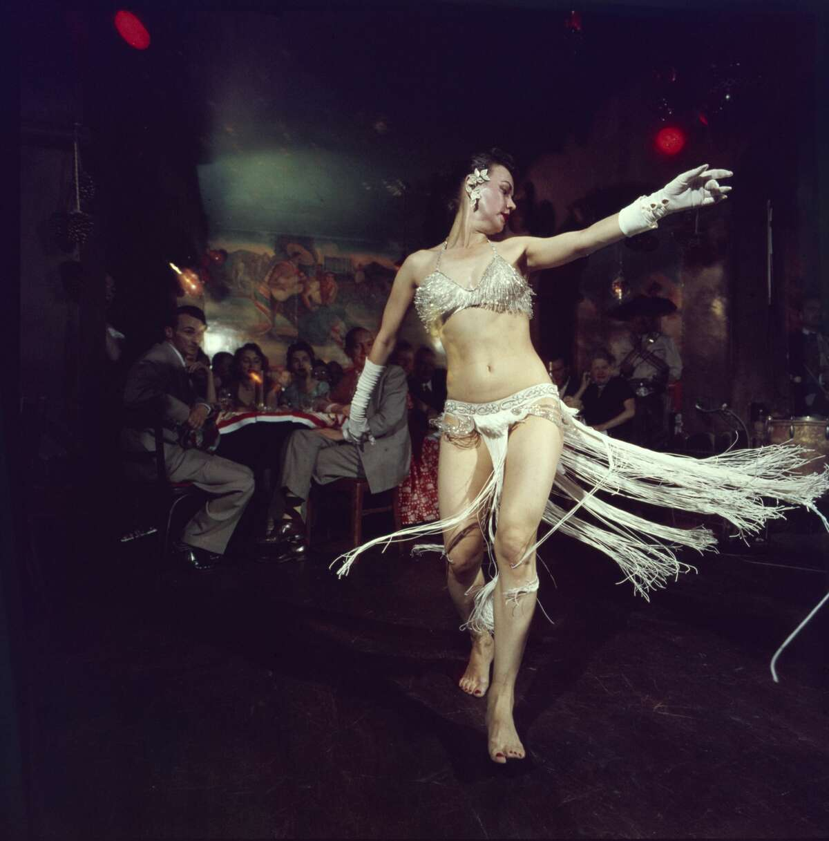 A dancers dressed in a white sequinned and fringed bikini and elbow gloves as she performs for patrons at the Sinaloa Club, San Francisco, California, 1956. (Photo by Nat Farbman/The LIFE Picture Collection/Getty Images)