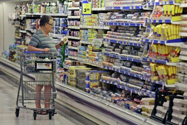 A shopper looks at an item in the dairy section of a Kroger grocery store in Richardson, Texas. Packaged food makers are trying to adapt their selling strategies as more people do their grocery shopping online.