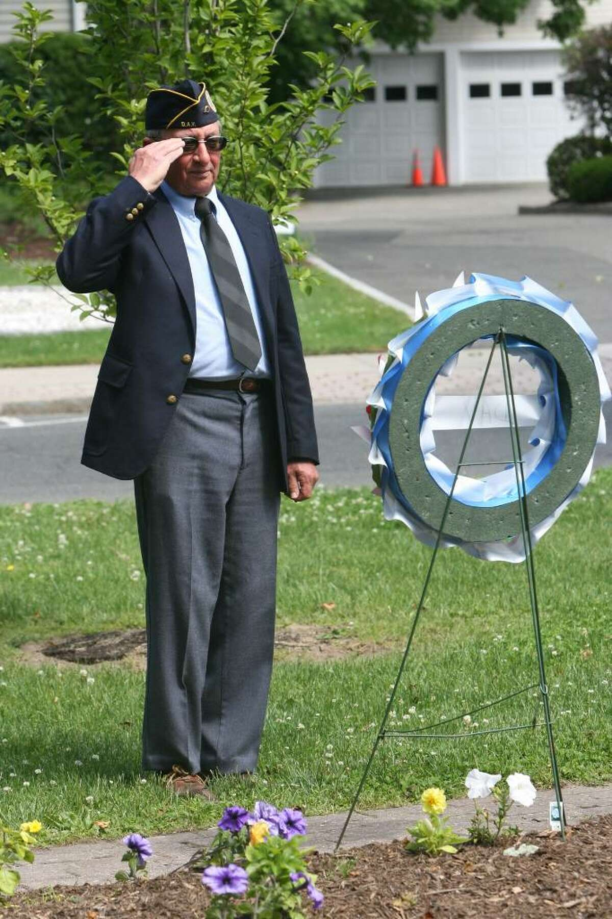 Veteran Mike Copelan, of DAV chapter 15, salutes during a wreath laying ceremony in Milford on Sunday morning.