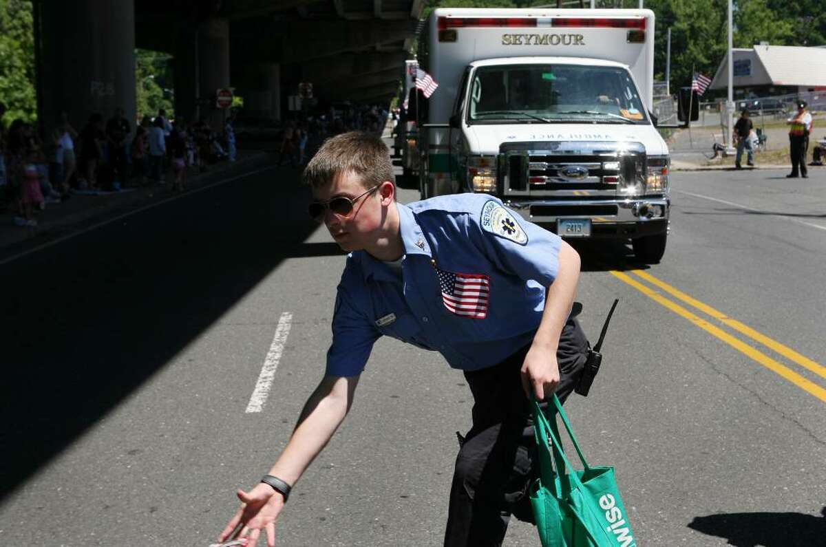 Seymour EMT Joshua Wood throws candy to children while marching in the Seymour Memorial Day parade on Sunday morning.