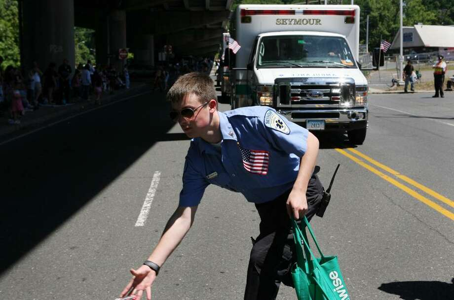 Seymour EMT Joshua Wood throws candy to children while marching in the Seymour Memorial Day parade on Sunday morning. Photo: B.K. Angeletti / Connecticut Post