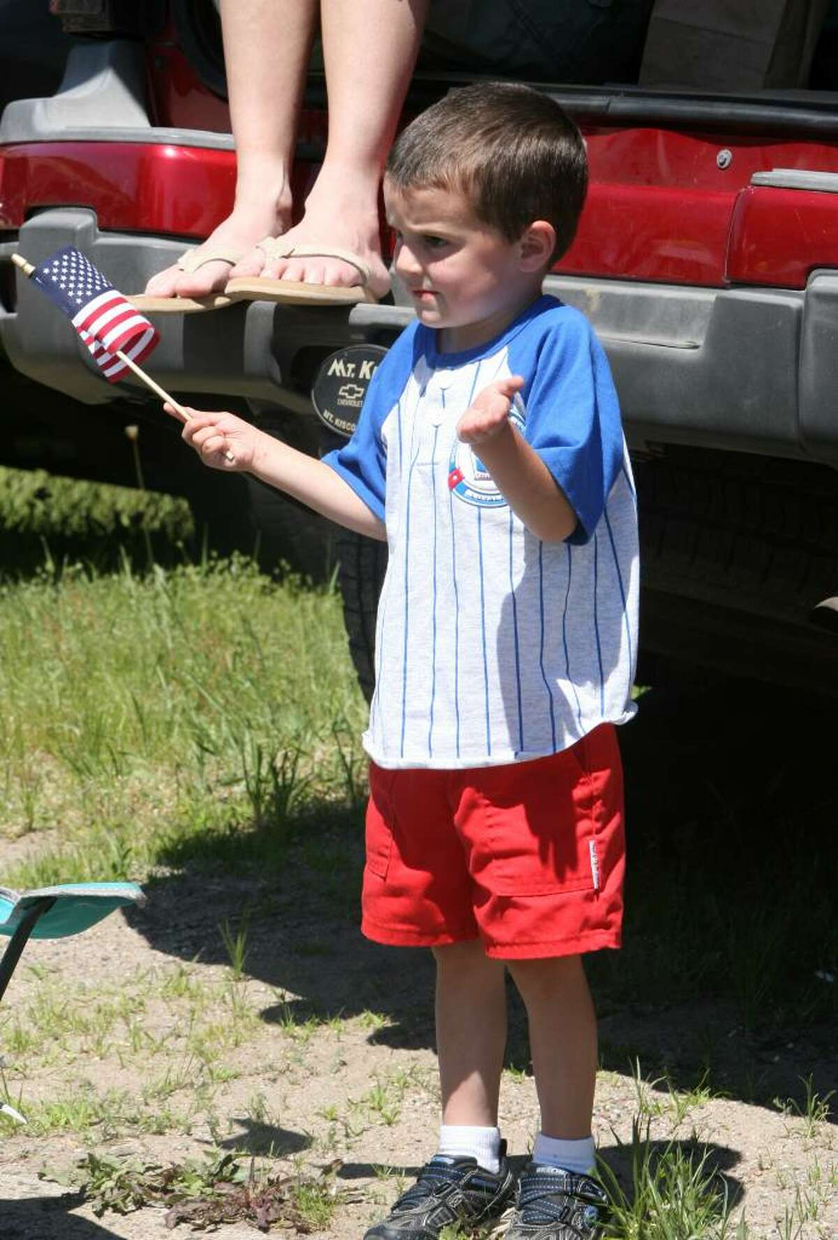 James Rich, 4 of Seymour, waves to marchers in the Seymour Memorial Day parade on Sunday morning.