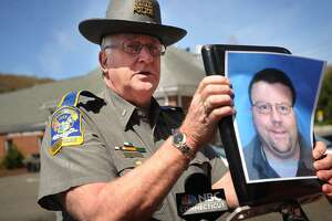 State police spokesman Lt. Paul Vance holds up a photo of Oxford homicide suspect Scott Gellatly,the subject of state police manhunt in the killing of his estranged wife, Lori Gellatly, in Oxford, Conn. on Wednesday, May 7, 2014.