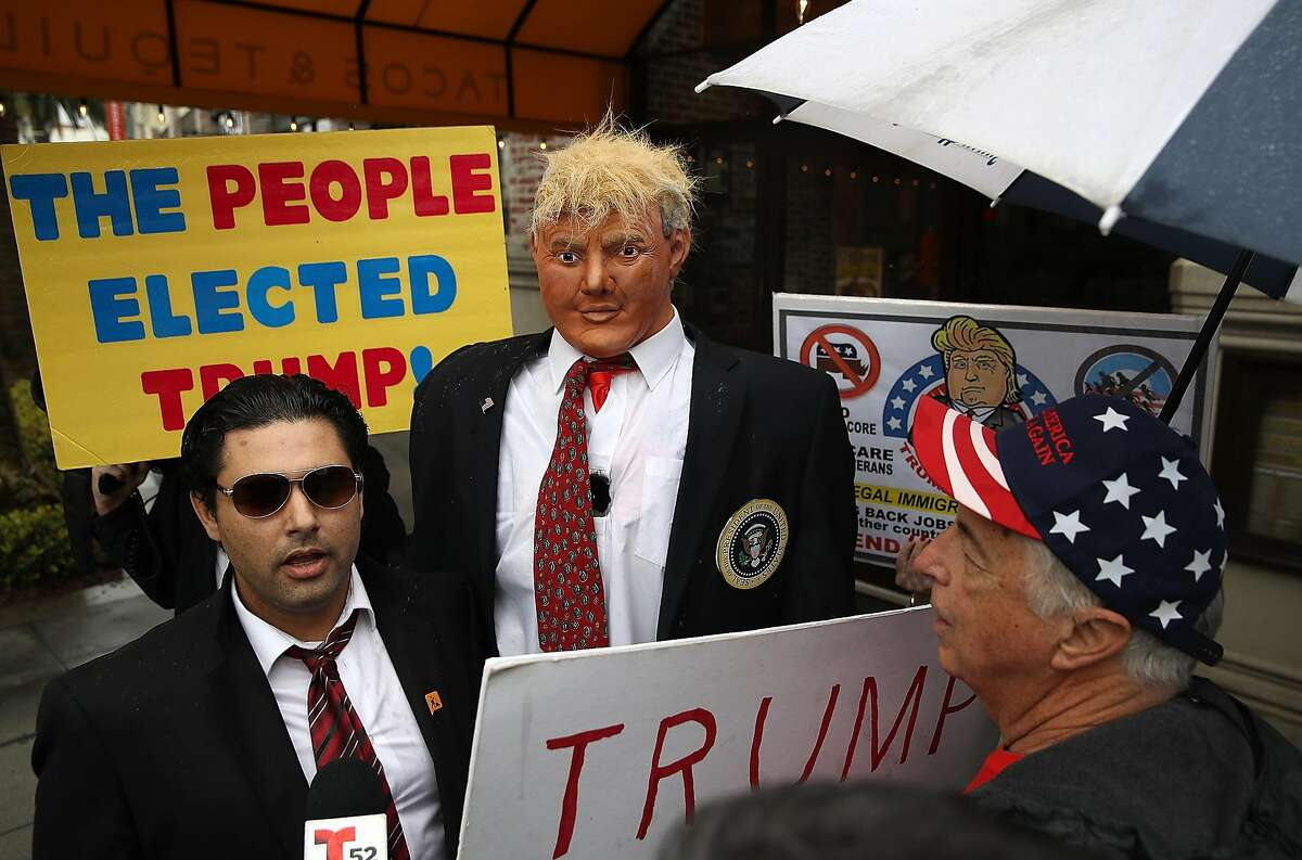 BREA, CA - FEBRUARY 27: Supporters of U.S. President Donald Trump surround a man with a mannequin dressed as President Trump during a rally in favor of the