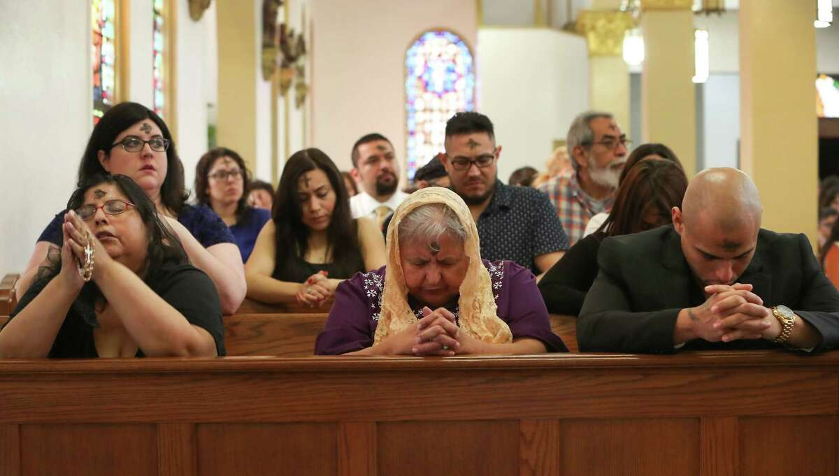 Angeline Young (l-r), Lisa Gutierrez and Michael Botello prays after receiving ashes by at Our Lady of Guadalupe Catholic Church during Ash Wednesday Mass, Wednesday, March 1, 2017, in Houston. Catholics mark the beginning of Lent with Ash Wednesday. Throughout the day, thousands will attend Masses and Services during which they will receive ashes across their foreheads in a ceremony known as the