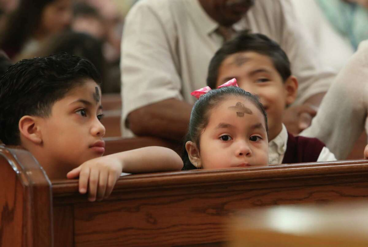 Our Lady of Guadalupe school kindergarteners Christian Zamora (left) and Evelyn Gonzalez pray after receiving ashes during Ash Wednesday Mass, Wednesday, March 1, 2017, in Houston. Catholics mark the beginning of Lent with Ash Wednesday. Throughout the day, thousands will attend Masses and Services during which they will receive ashes across their foreheads in a ceremony known as the