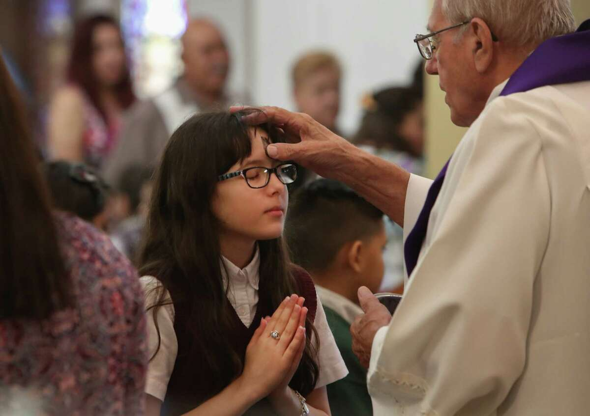 """Our Lady of Guadalupe school 6th grader Lauryn Olivarez is given ashes by Father Richard Johnston during Ash Wednesday Mass, Wednesday, March 1, 2017, in Houston. Catholics mark the beginning of Lent with Ash Wednesday. Throughout the day, thousands will attend Masses and Services during which they will receive ashes across their foreheads in a ceremony known as the ?'imposition?"""" of ashes. The ashes symbolize penance and are a reminder of our mortality."""