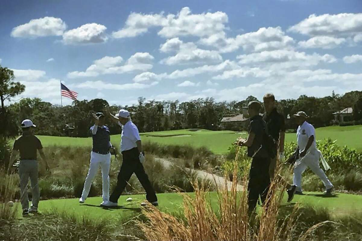 US President Donald Trump (3rd L) high-fives Japan's Prime Minister Shinzo Abe (2nd L) while playing golf in Florida on February 11, 2017. After reportedly hitting it off in the Oval Office, President Donald Trump and his Japanese counterpart Shinzo Abe teed off on the golf course on February 11, and discussed US-Asia engagement. / AFP PHOTO / JIJI PRESS / JIJI PRESS / Japan OUTJIJI PRESS/AFP/Getty Images