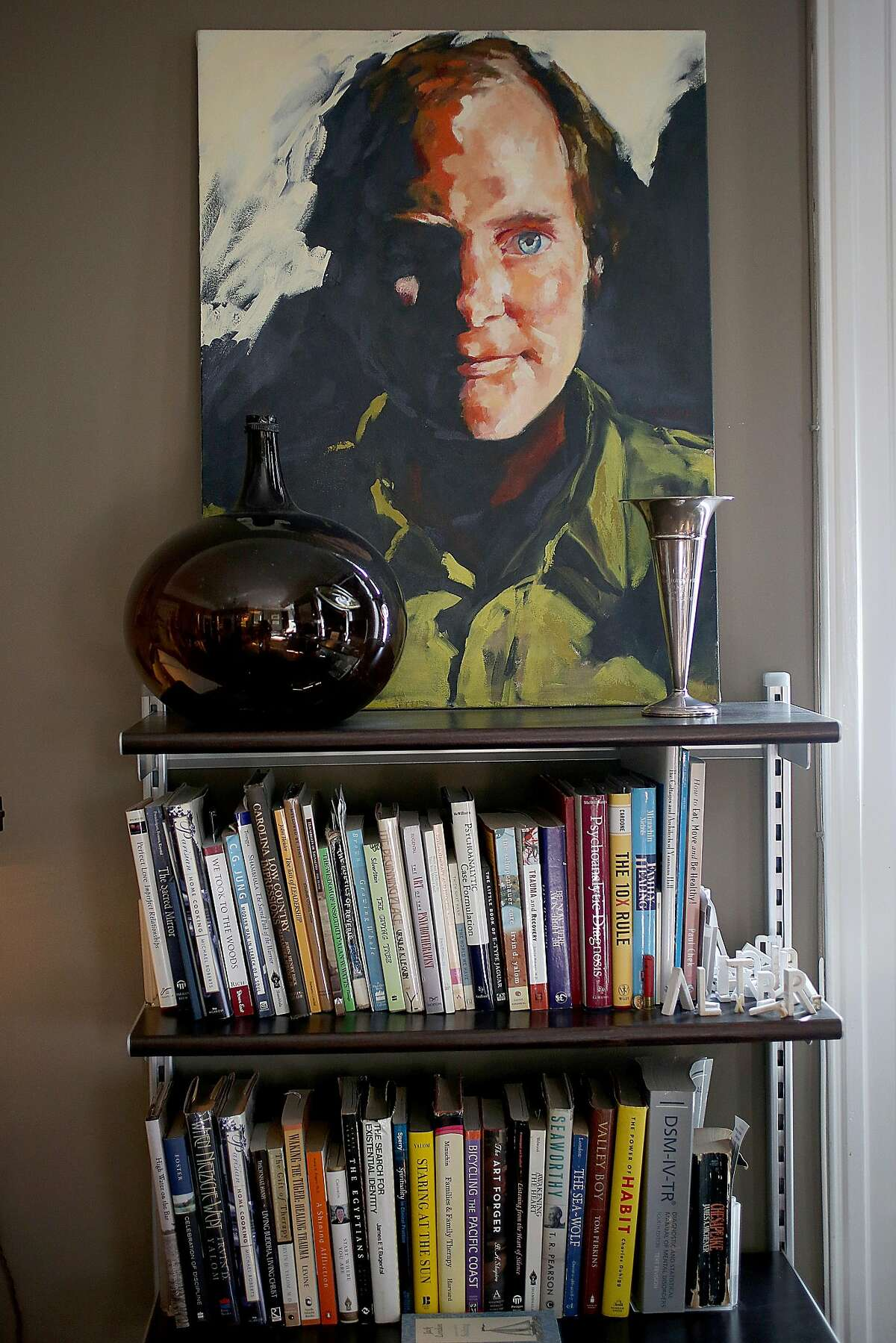 Maria Costa did a portrait (top) of lighting designer Robert Long which hangs above his bookcase at home on Monday, February 27, 2017, in Oakland, Calif.