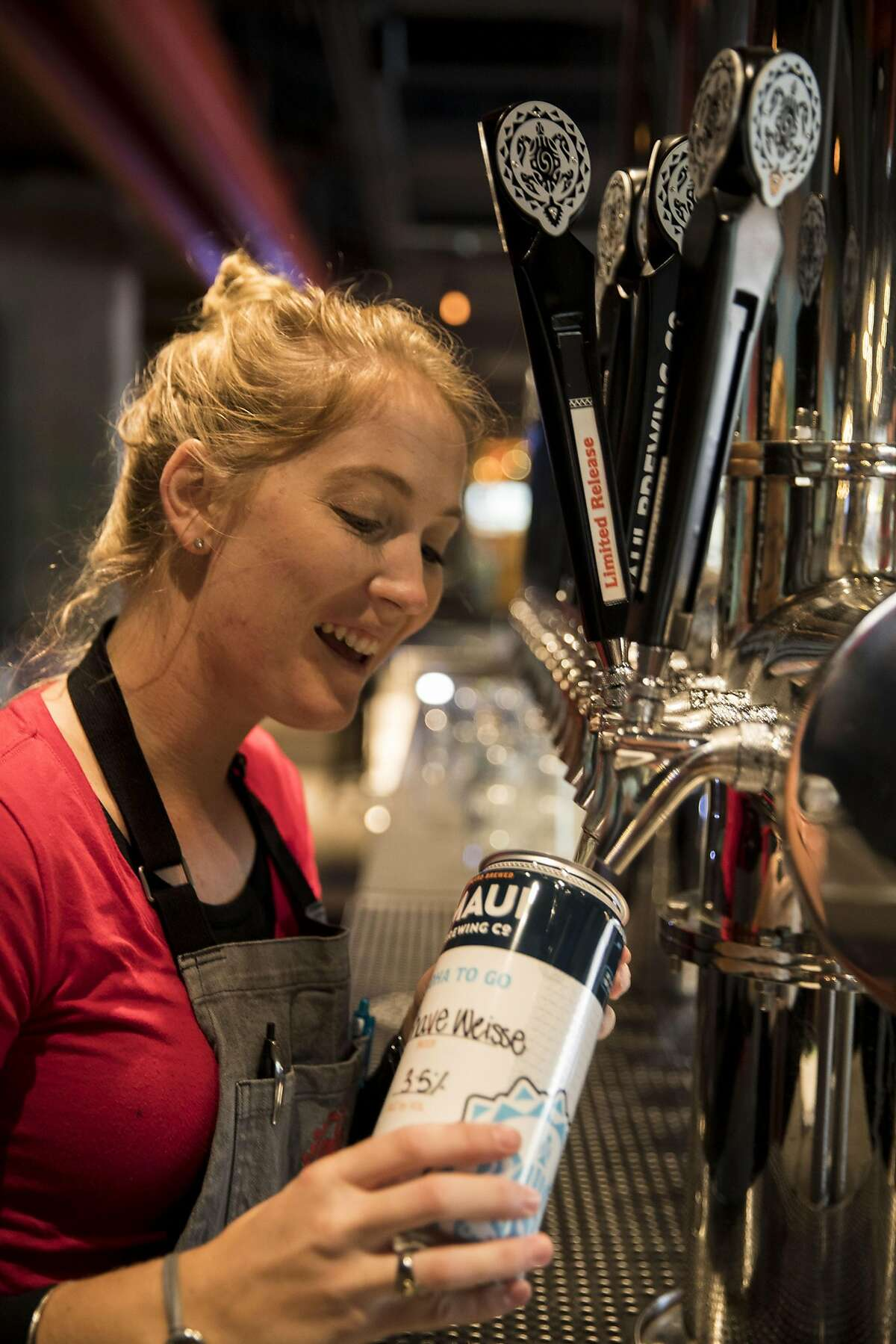 HONOLULU, HI - FEBRUARY 24: Bartender Dianne Husband fills a growler with Shave Weisse at Maui Brewing Company, located in the second floor of the Holiday Inn Resort Waikiki Beachcomber, on February 24, 2017 in Honolulu, Hawaii.
