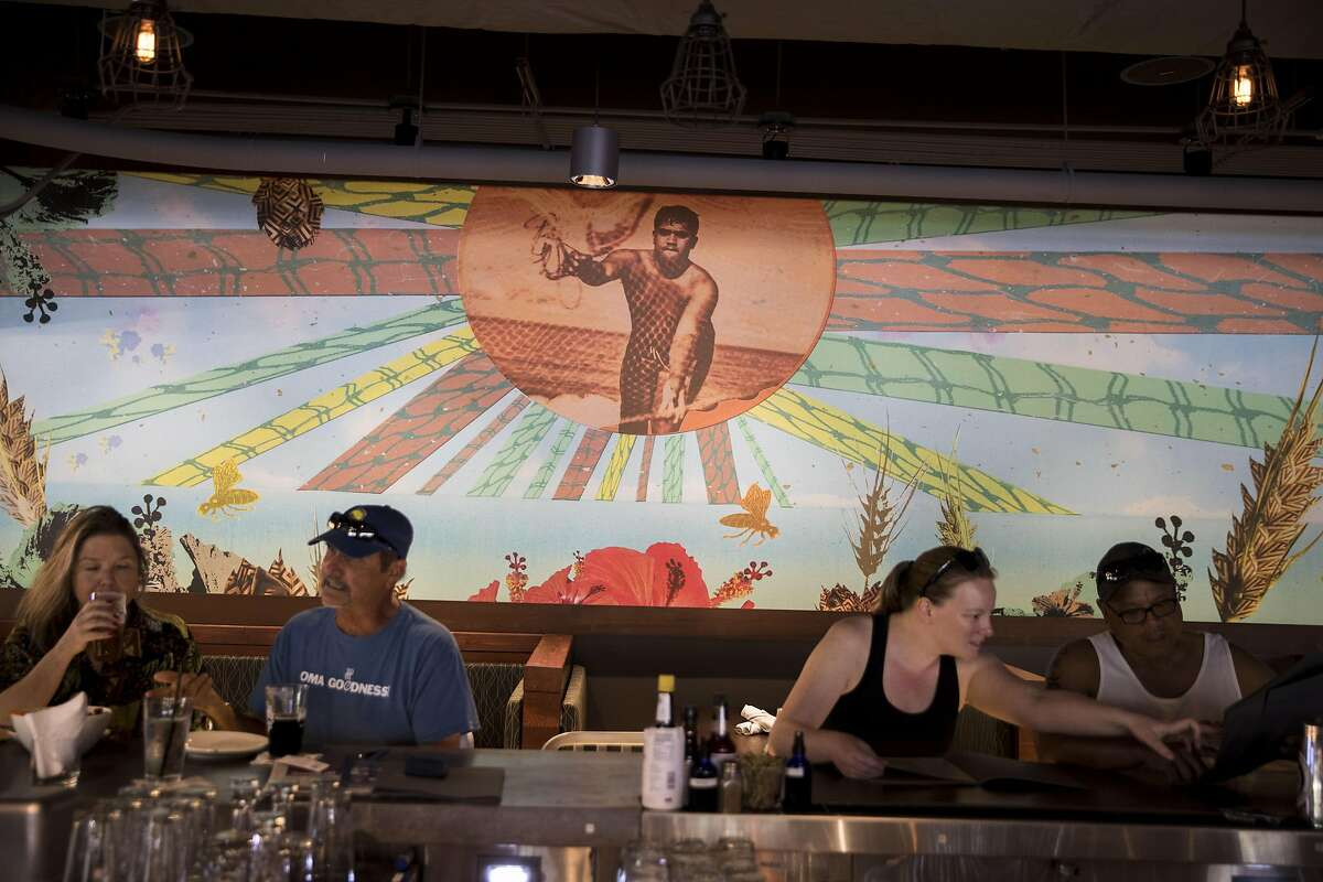 HONOLULU, HI - FEBRUARY 24: A mural by Big Island artist Margo Ray acts as a backdrop to patrons sitting at the bar at Maui Brewing Company, on the second floor of the Holiday Inn Resort Waikiki Beachcomber, on February 24, 2017 in Honolulu, Hawaii.