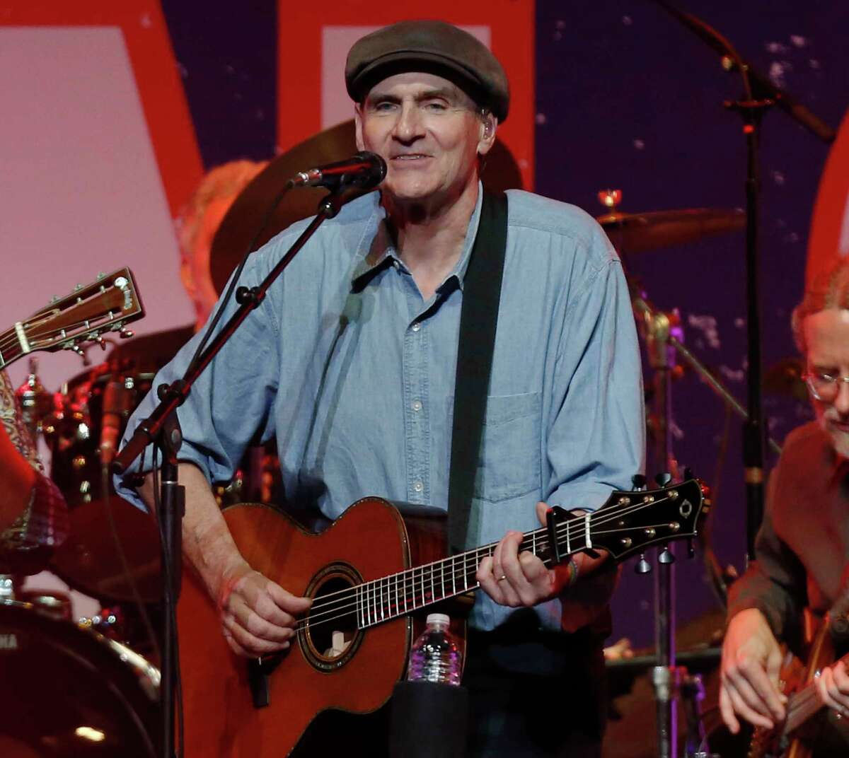 FILE - In this May 30, 2013 file photo, James Taylor performs at the Boston Strong Concert: An Evening of Support and Celebration at the TD Garden, in Boston. (Photo by Bizuayehu Tesfaye/Invision/AP, file)