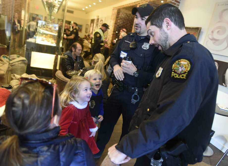"Greenwich Police Officers Brian Andronaco, left, and Wally Wallace chat with 4-year-olds at a recent ""Coffee With A Co"" gathering on Greenwich Avenue. Photo: / Hearst / Tyler Sizemore"