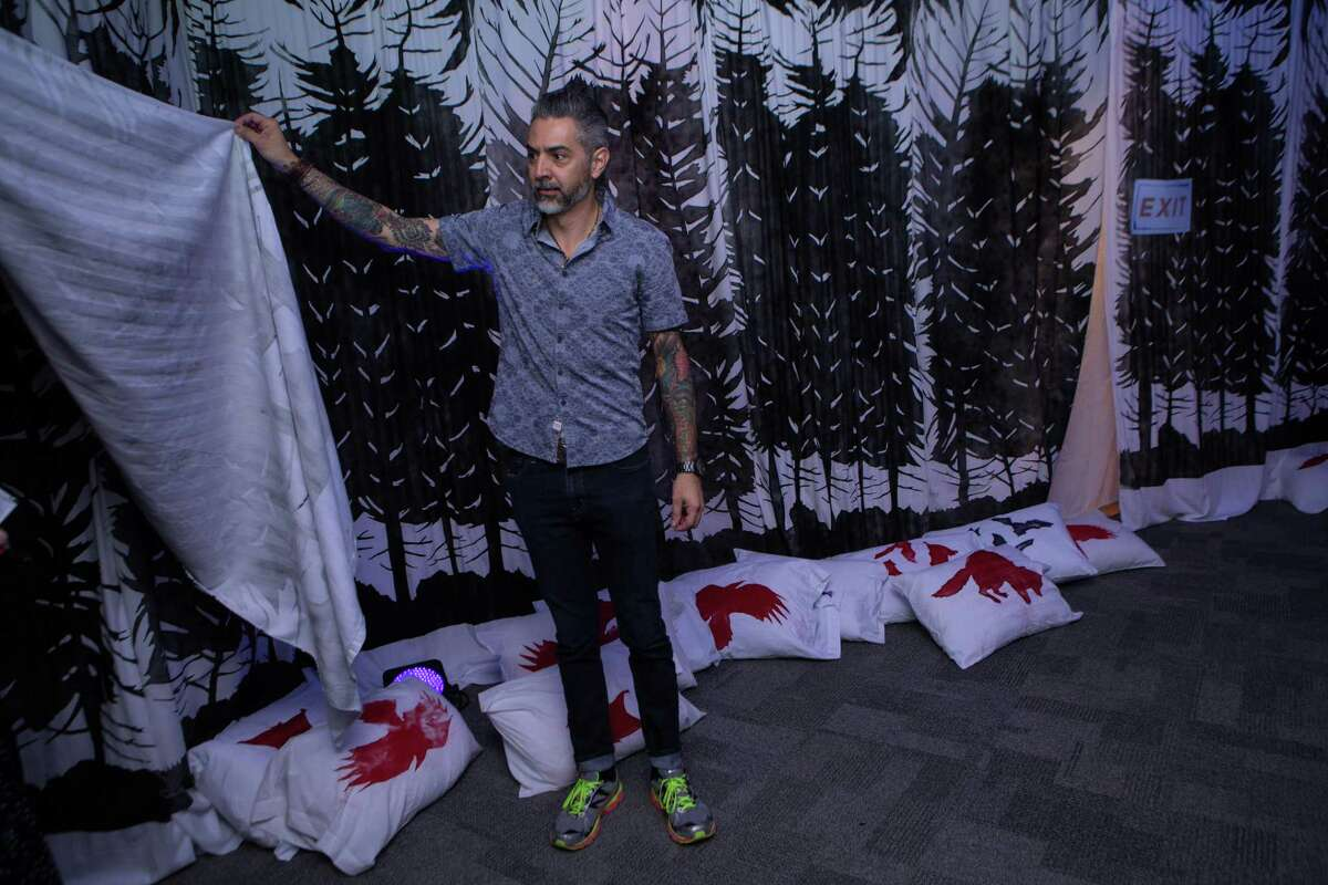 """Artist Richard Armendariz pulls back a sheet to welcome guests into the bedsheet tent in """"The Dream Keeper,"""" his installation at the DoSeum."""