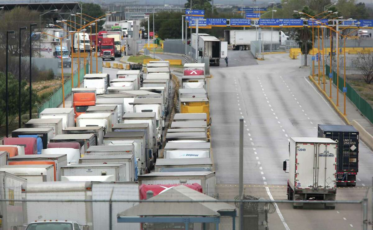 File photo of two trucks, right, leaving the U.S. as a long line of trucking traffic waits to enter the U.S. from Mexico at the World Trade Bridge in Laredo, TX, on Friday, Jan. 27, 2017. President Donald Trump, within his first week in office, floated the idea for a 20 percent tariff on Mexican goods that sent executives here and across the border scrambling to fend off the attack. The tariff idea never went any where, but animosity between the U.S. and Mexico increased throughout the year as Trump moved forward with plans to build a border wall between the two nations and to renegotiate NAFTA.