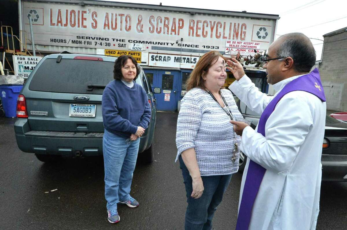 St. Matthew's Church Father Tomi Thomas makes a stop at LaJoie's Auto and Scrap Recycling Co. on Meadow St. and administers the ashes for Pam Falcone as Joan Christensen waits her turn on Ash Wednesday March 1, 2017 in Norwalk Conn.