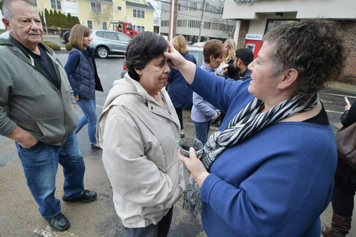 Liz Reid with St. Matthew's Church places ashes on the forehead of Marie Satta as husband Vincent waits after they walked up to Salon Moda which was a scheduled stop for the church group on Ash Wednesday March 1, 2017 in Norwalk Conn.