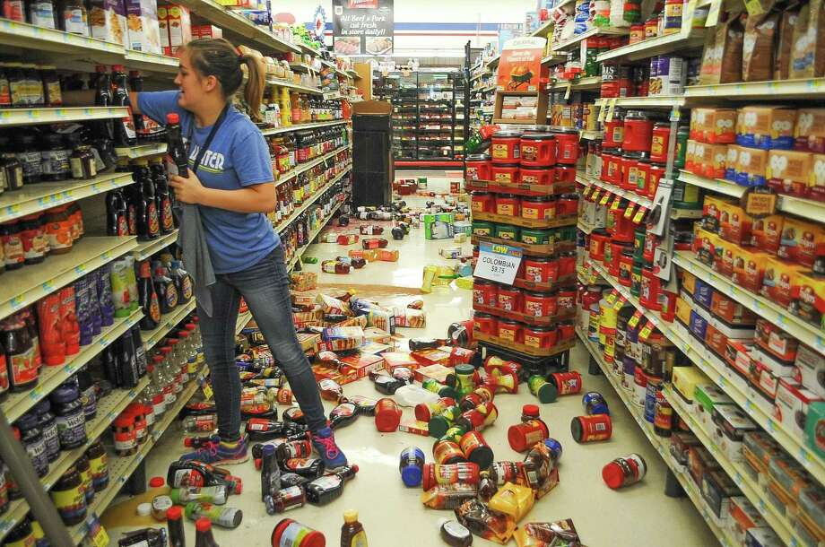 Employee Talia Pershall, 16, puts syrup back on a shelf while cleaning up at White's Foodliner grocery store Saturday, Sept. 3, 2016 in Pawnee, Okla., following a 5.6 magnitude earthquake that hit north-central Oklahoma. Photo: David Bitton /Associated Press / The News Press