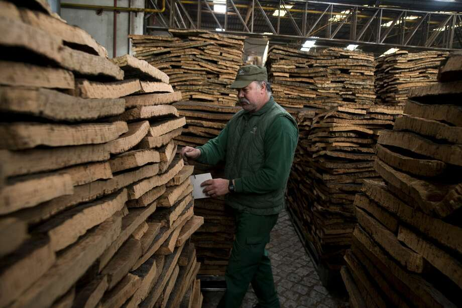A worker marks cork bark planks in a storage area at the Amorim & Irmaos SA, factory, operated by Corticeira Amorim SGPS SA, in Santa Maria da Feira, Portugal, on Friday, Feb. 24, 2017. Photo: Paulo Duarte/Bloomberg
