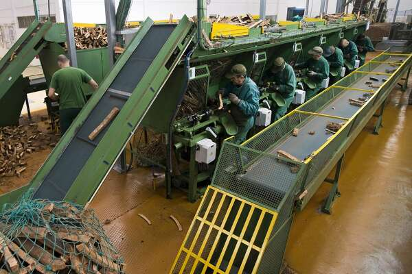 Workers make natural cork stoppers using a machine to punch out cylindrical stoppers from cork strips at the Amorim & Irmaos SA, factory, operated by Corticeira Amorim SGPS SA, in Santa Maria da Feira, Portugal, on Friday, Feb. 24, 2017.