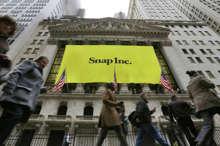 """People pass by the New York Stock Exchange after the banner for the Snap Inc. IPO was raised on the building's facade Wednesday. Snap Inc. is expected to start trading on the New York Stock Exchange on Thursday under the symbol """"SNAP."""" Photo: Richard Drew /Associated Press / AP"""