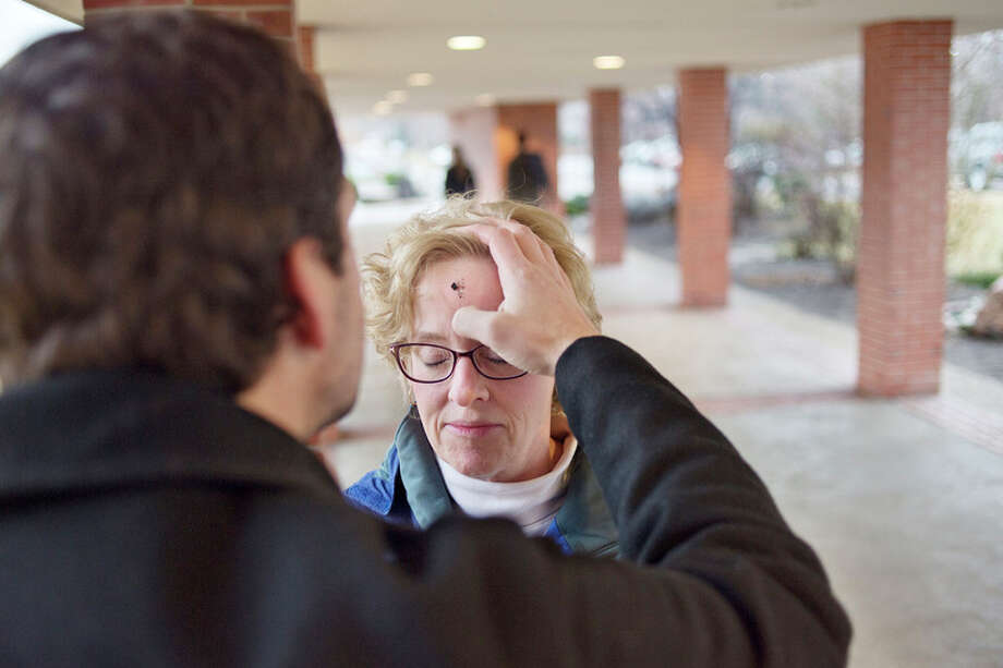 BRITTNEY LOHMILLER | blohmiller@mdn.net  St. John's Episcopal Church Rev. Ken Hitch spreads ashes on Midland resident Beth Shoemaker's forehead outside of the Greater Midland Community Center on Ash Wednesday. / Midland Daily News