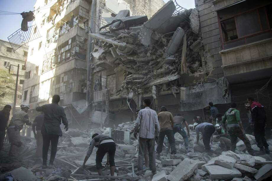 TOPSHOT - Syrian civilians and rescuers gather at site of government forces air strikes in the rebel held neighbourhood of Al-Shaar in Aleppo on September 27, 2016.  Syria's army took control of a rebel-held district in central Aleppo, after days of heavy air strikes that have killed dozens and sparked allegations of war crimes.   / AFP PHOTO / KARAM AL-MASRIKARAM AL-MASRI/AFP/Getty Images Photo: KARAM AL-MASRI, Stringer / AFP or licensors