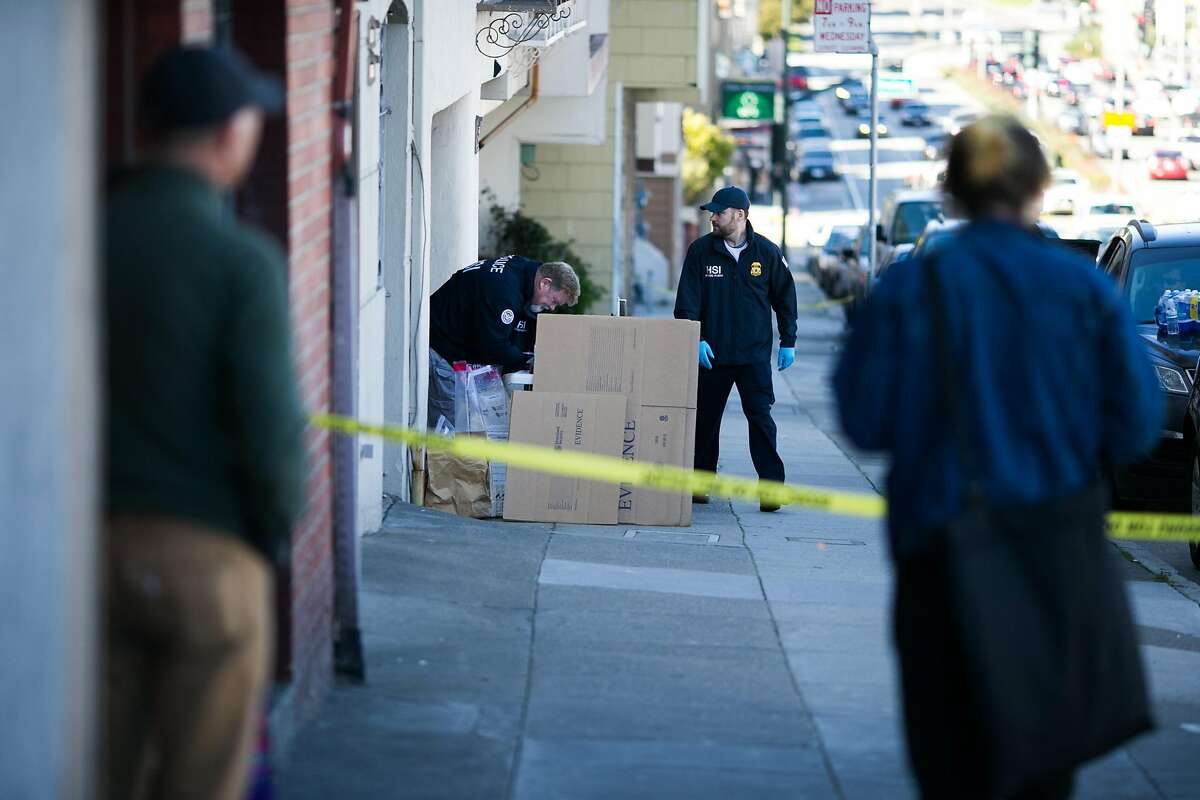 Pedestrians gather along the sidewalk as Homeland Security Investigation agents investigate a residence on 19th Avenue between Irving Street and Judah Street in San Francisco, Calif. Wednesday, March 1, 2017.