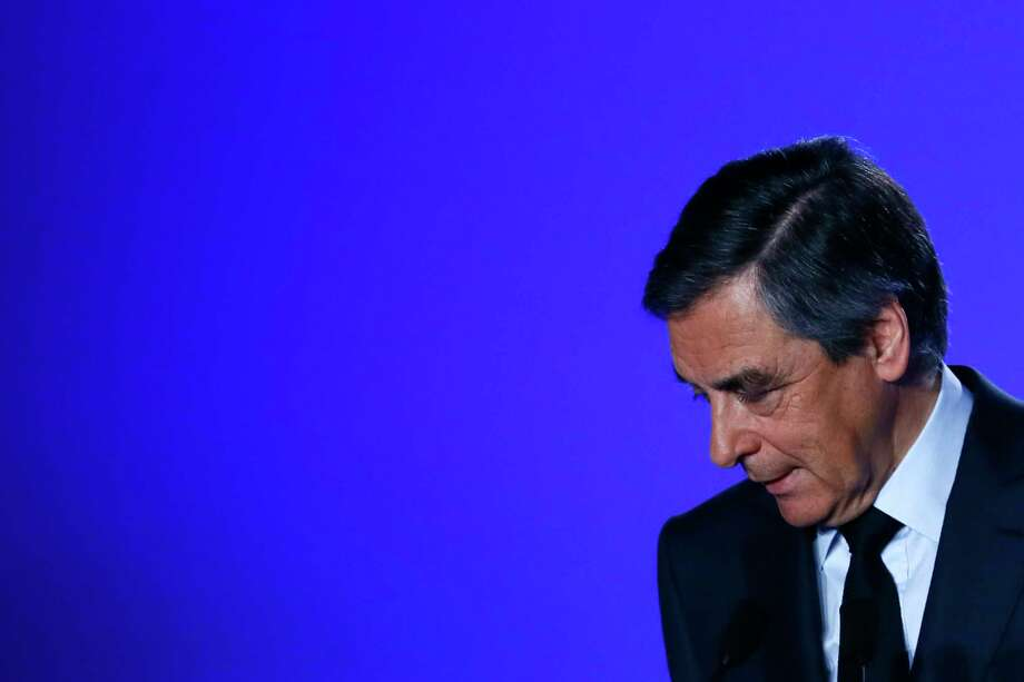 Conservative presidential candidate Francois Fillon leaves after delivering his speech at his campaign headquarters in Paris, Wednesday, March 1, 2017. Fillon is refusing to quit the race despite receiving a summons Wednesday to face charges for alleged fake parliamentary jobs for his family. (AP Photo/Francois Mori) Photo: Francois Mori, STF / Copyright 2017 The Associated Press. All rights reserved.