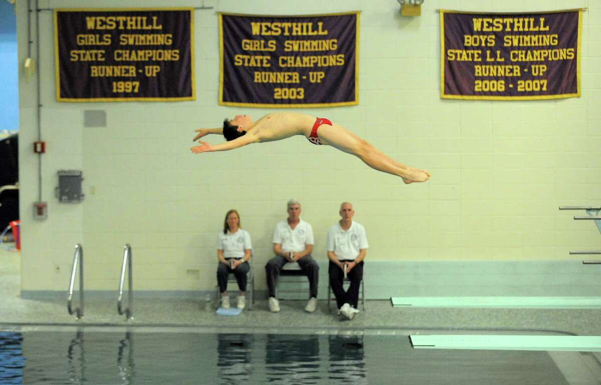 New Canaan George Moore competes in the FCIAC diving championship at Westhill High School pool in Stamford, Conn. on March 1, 2017.