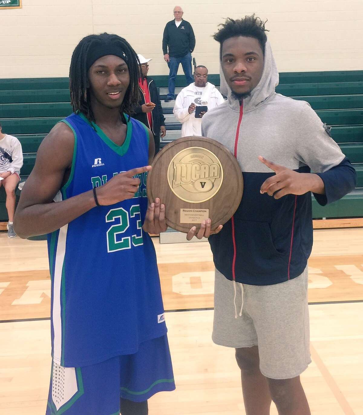 Conroe High School graduates Tremont Moore, left, and Marcus Keyser pose with the NJCAA Region V Division III championship plaque this past weekend.
