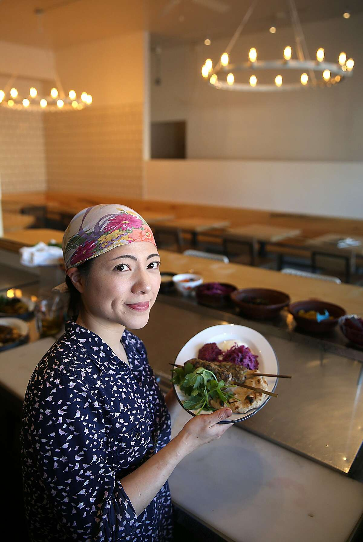 Chef Traci Matsumoto-Esteban shows a plate of lamb kebabs on grilled flatbread with mashed beets, sauerkraut salad, pickled chiles, and strained yogurt at the Kebabery on Tuesday, February 28, 2017, in Oakland, Calif.