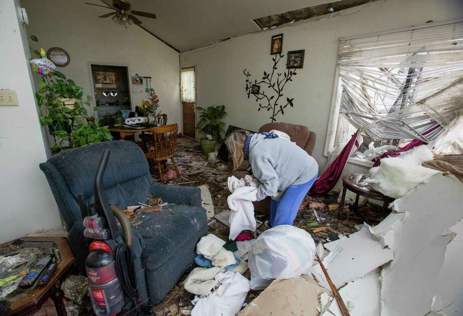 "Debbie Loughridge is seen going through rubble in her living room in Naplate, Ill., Wednesday, March 1, 2017. She rode out the storm in the bathtub. ""All I heard was the wind and the breaking glass. Like an explosion of glass,"" Loughridge said. In the small community of Naplate, next to Ottawa, about a quarter of the roughly 200 homes were damaged, Fire Chief John Nevins said. (AP Photo/Teresa Crawford) Photo: Teresa Crawford, STF / AP"