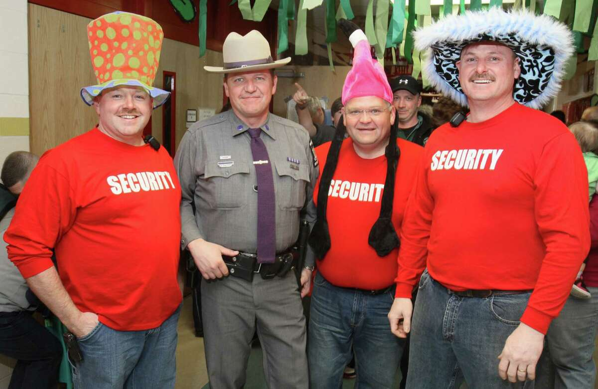 Glens Falls, NY - March 4, 2011 - (Photo by Joe Putrock/Special to the Times Union) - NYS Trooper Tim Pratt(2nd from left) poses with members of volunteer security staff Sean Baxter(right) Andy Laing(2nd from right) and Brian Huntley(right) during the South High Marathon Dance to benefit individuals, families and organizations in need of financial assistance. Trooper Pratt has has only missed seven Marathon Dances, due to miltary service, since it was started when he was a Junior in High School in 1978. ORG XMIT: MER2017021714402128