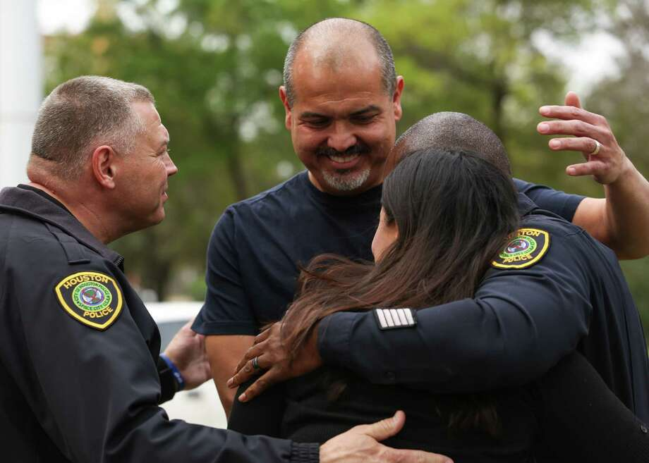 Danny Cortez, brother of officer Ronny Cortez, and Jazmin Muñoz, wife of officer Jose Muñoz, embrace with chaplain Monty B. Montgomery, left, and HPD Executive Assistant Chief Troy Finner. Photo: Yi-Chin Lee / Houston Chronicle, HPD Presser / Houston Chronicle 2017