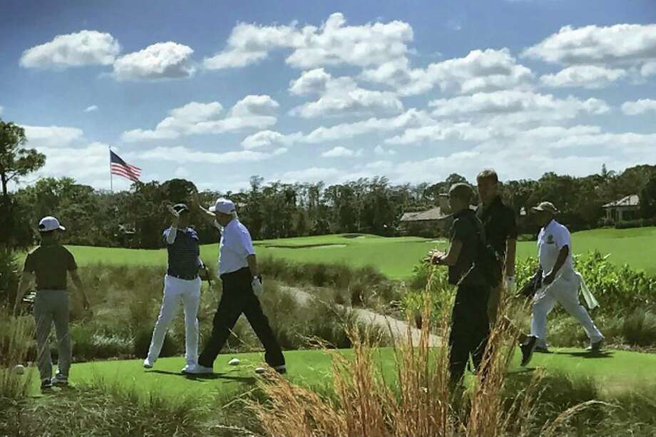 US President Donald Trump (3rd L) high-fives Japan's Prime Minister Shinzo Abe (2nd L) while playing golf in Florida on February 11, 2017. After reportedly hitting it off in the Oval Office, President Donald Trump and his Japanese counterpart Shinzo Abe teed off on the golf course on February 11, and discussed US-Asia engagement. / AFP PHOTO / JIJI PRESS / JIJI PRESS / Japan OUTJIJI PRESS/AFP/Getty Images Photo: JIJI PRESS, Stringer / AFP