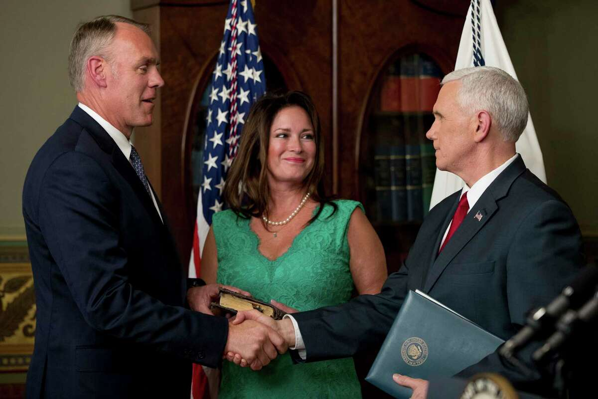 Vice President Mike Pence, right, shakes hands after administering the oath of office to Interior Secretary Ryan Zinke, left, Wednesday, March 1, 2017, in the Eisenhower Executive Office Building on the White House complex in Washington. Also pictured is Ryan Zinke's wife Lolita Hand, center. (AP Photo/Andrew Harnik) ORG XMIT: DCAH104