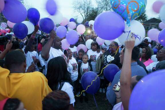 """De'Maree Adkins' father, Detram Adkins, and mother, Latoyia Thomas, address the crowd assembled for a balloon release in memory of their 8-year-old daughter, who loved to write and was called a """"girly-girl."""""""