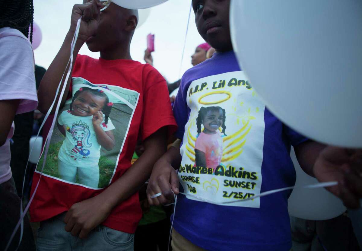 Children wear shirts with De'Maree Adkins' photo during a balloon release that featured the 8-year-old's favorite colors - purple and pink.