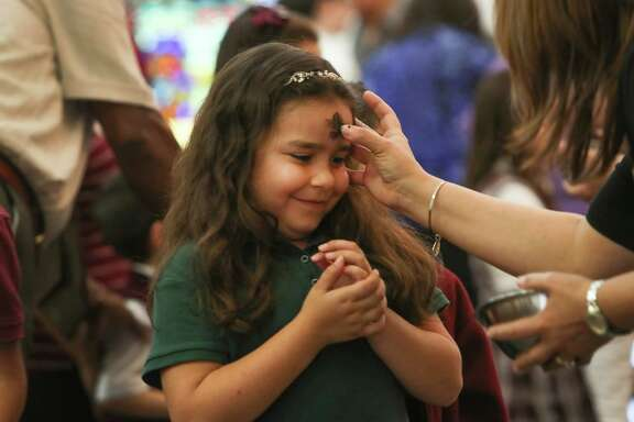 Our Lady of Guadalupe school 2nd grader Jazlyn Olivares is given ashes by Principal Irazema Ortiz during Ash Wednesday Mass, Wednesday, March 1, 2017, in Houston.  Catholics mark the beginning of Lent with Ash Wednesday. Throughout the day, thousands will attend Masses and Services during which they will receive ashes across their foreheads in a ceremony known as the ÒimpositionÓ of ashes.  The ashes symbolize penance and are a reminder of our mortality.