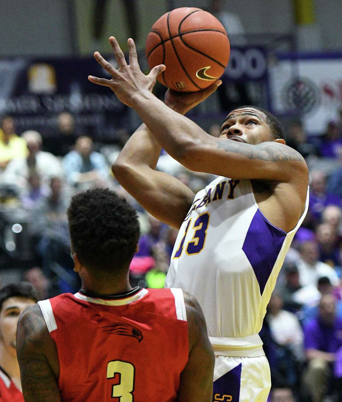 UAlbany's #13 David Nichols gets a shot off past Hartford defender Jalen Ross during the first round game of the America East Conference Tournament Wednesday March 1, 2017 in Albany, NY. (John Carl D'Annibale / Times Union)