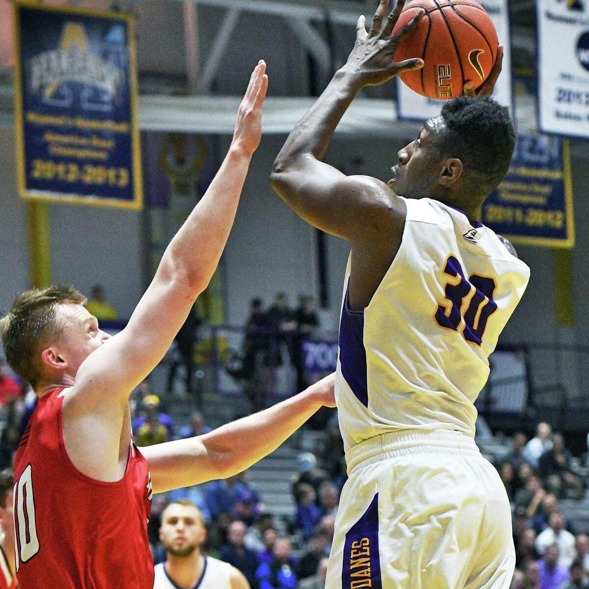 UAlbany's #30 Travis Charles, right, fires off a shot as gets a shot off past Hartford's #10 John Carroll defends during the first round game of the America East Conference Tournament Wednesday March 1, 2017 in Albany, NY. (John Carl D'Annibale / Times Union)