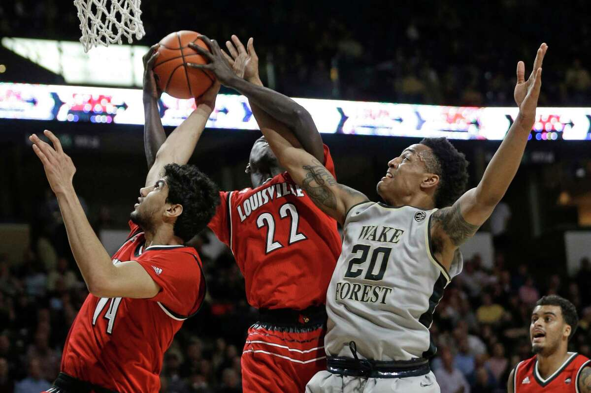 Wake Forest's John Collins (20) competes against Louisville's Deng Adel (22) and Anas Mahmoud (14) for a rebound during the first half of an NCAA college basketball game in Winston-Salem, N.C., Wednesday, March 1, 2017. (AP Photo/Chuck Burton) ORG XMIT: NCCB107