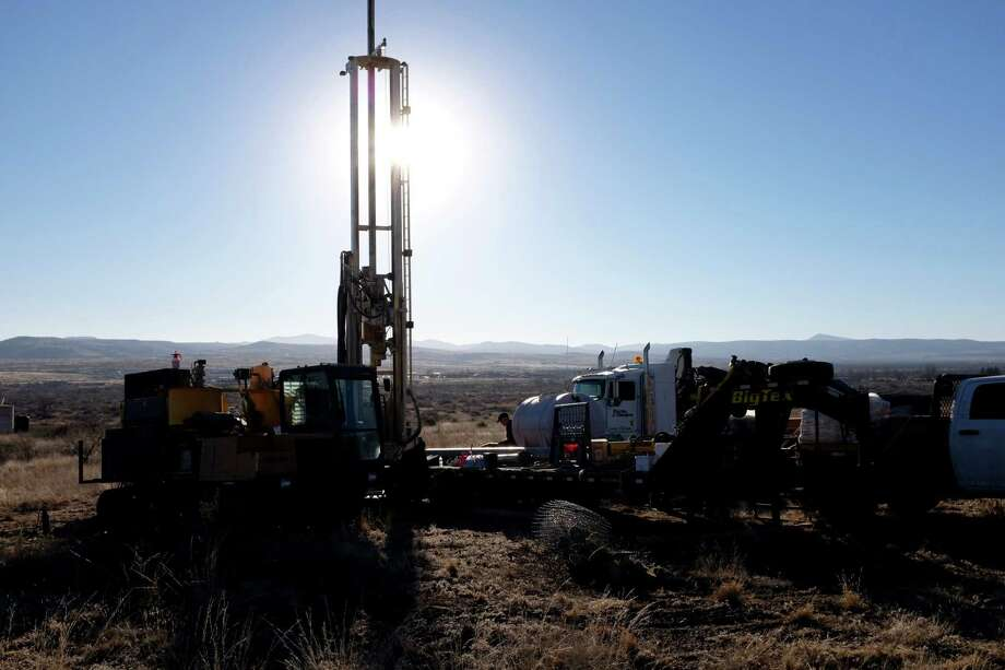 Scientists from the University of Texas and a contractor, Nanometrics, install a seismometer on a hillside owned by Sul Ross University in Alpine, Texas. (Lydia DePillis/Houston Chronicle)