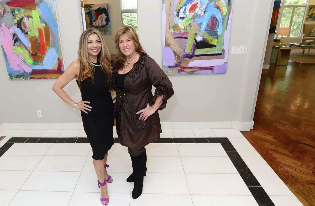 Westport artist Sholeh Janati, an Iranian immigrant, and Lisa Jones, a Fairfield Realtor, at a home for sale at 345 Governors Lane on Thursday in Fairfield . Jones hopes to help sell a surplus of luxury real estate by turning homes into art galleries.