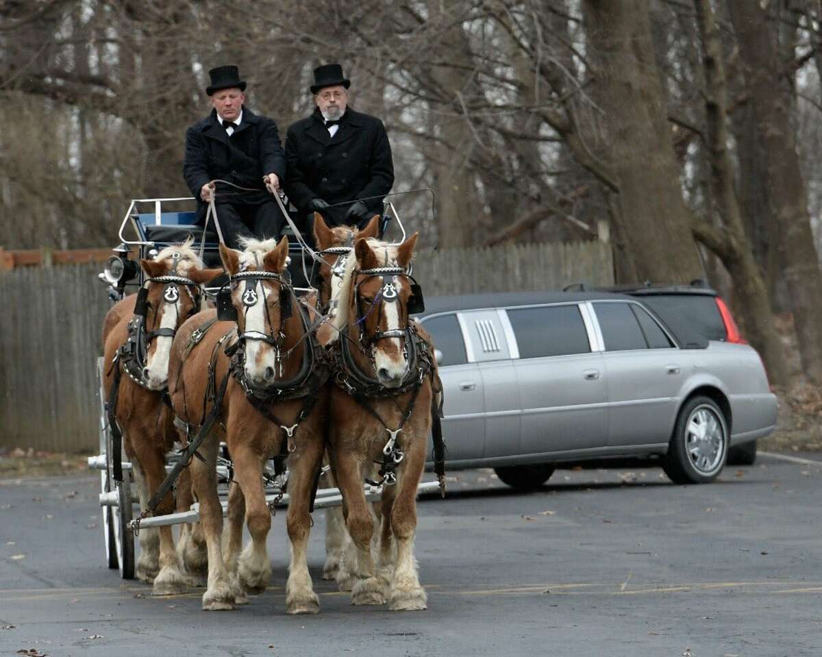 The casket of J. Kenneth Ray, the long-time businessman and owner of John Ray & Sons oil distributors, was carried through city streets Thursday morning as friends and family said their final goodbyes to the man who died this week at 95. The casket sat atop a 1898 Studebaker carriage that was drawn by four draft horses. (Skip Dickstein / Times Union)