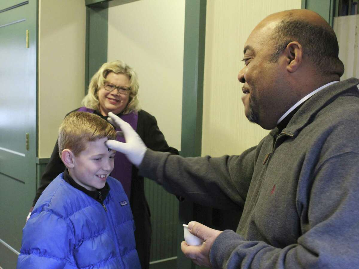 Father Reggie Norman of Our Lady of Fatima Parish drawing a cross of ashes on James Dineen's forehead at Wilton train station on Wednesday, March 1.