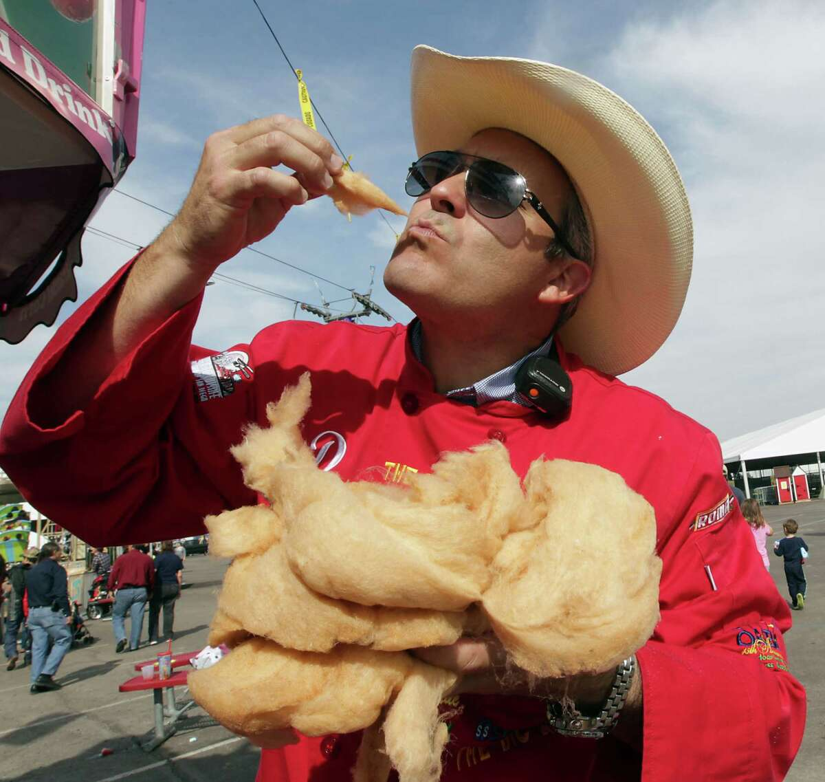 """RSC's Dominic """"The Midway Gourmet"""" Palmieri takes a bite of the Bacon Cotton Candy at the Houston Livestock Show and Rodeo Carnival Saturday, Feb. 23, 2013, in Houston. ( James Nielsen / Houston Chronicle )"""