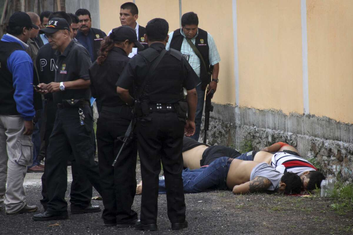 Police stand next to the bodies of four men that were left next to a wall in the town of Medellin, near Veracruz, Mexico, Wednesday Jan. 11, 2012. All four men showed signs of torture. More than 47,000 people have been killed in drug violence in the five years since President Felipe Calderon launched a military crackdown against drug cartels, federal prosecutors said Wednesday.