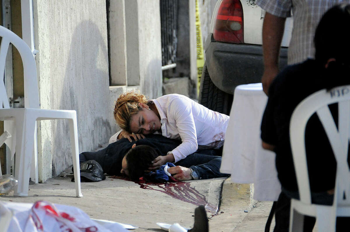A woman cries on June 25, 2016 over the body of a relative who was shot dead on the eve when unknown gunmen arrived at a party and opened fire, in Veracruz, eastern Mexico. The brother and the son of an official of the troubled Mexican state of Veracruz and his three bodyguards were shot on Friday when they were at a party, according to reports by the region's prosecution and a judicial source. Veracruz is beset by murders and disappearances linked to drug cartels.